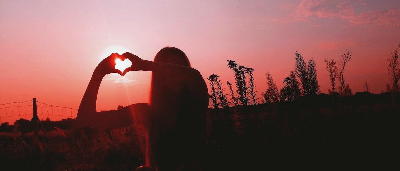Foto: Frau bildet bei Sonnenuntergang mit Händen ein Herz