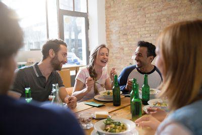 Bild: Menschen sitzen glücklich gemeinsam am Tisch
