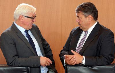 Außenminister Frank-Walter Steinmeier und Vizekanzler Sigmar Gabriel unterhalten sich auf einem Rednerpult. (Foto: dpa)