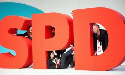 Foto: Mitglieder der Jugendorganisation der SPD (Jusos) posieren beim Bundesparteitag 2015 am SPD-Logo in Berlin.