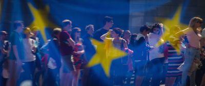 Foto: Eine Gruppe von Menschen sind hinter einer Europa-Flagge zu sehen