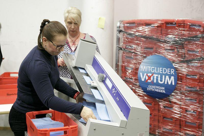 Foto: Freiwillige öffnen die Wahlbriefe mithilfe einer Hochleistungsschlitzmaschine