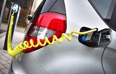 Foto: Elektroauto wird mit einem Stromkabel an einer Ladesäule mit Ökostrom geladen