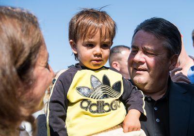 Sigmar Gabriel hält Muqnin, einen Flüchtlingsjungen aus Syrien, am 22.09.2015 bei der Besichtigung des Flüchtlingslagers Zaatari in Jordanien auf dem Arm, links daneben steht Aydan Özoguz (SPD), Staatsministerin für In