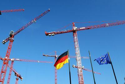 Kräne hinter einer Deutschland- und einer EU-Flagge. (Foto: dpa)