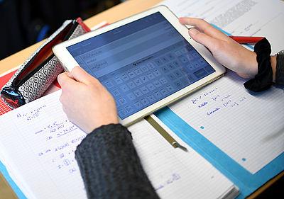 Foto: Ein Schüler errechnet eine Gleichung mit einem iPad im Matheunterricht.