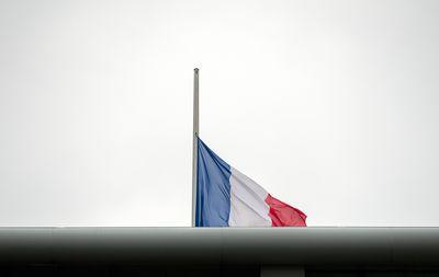 Foto: Die Französische Staatsflagge weht auf dem Dach der französischen Botschaft in Berlin auf Halbmast im Wind.