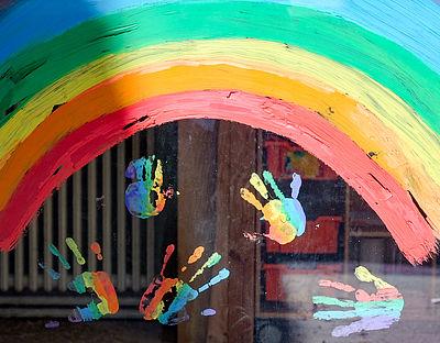 Foto: Kinderhände und ein Regenbogen sind an einer Kita zu sehen