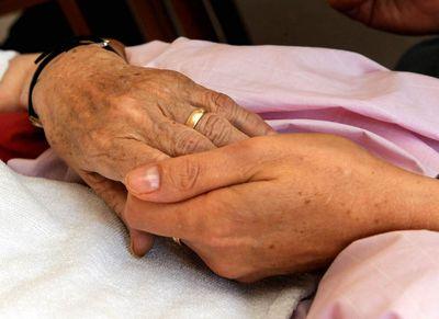 Die Hand einer kranken Frau wird von einer Pflegerin gehalten. Wenn todkranke Menschen nicht im Krankenhaus sterben wollen, muss rechtzeitig ein Platz im Hospiz oder eine gute Betreuung daheim organisiert werden. (Foto: dpa)