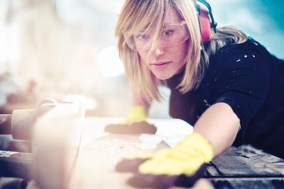 Symbolfoto Thema Arbeit: Handwerkerin arbeitet mit Gehörschutz