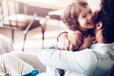 Symbolfoto Thema Familie: Vater umarmt sein Kind