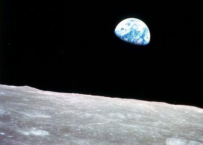 Foto: Blick auf die Erde, die über der Mondoberfläche vor dem Hintergrund des tierschwarzen Weltalls aufgeht.