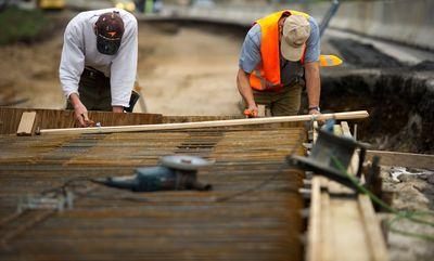Foto: Bauarbeiter arbeiten an einer Verbreiterung einer Autobahnbrücke.