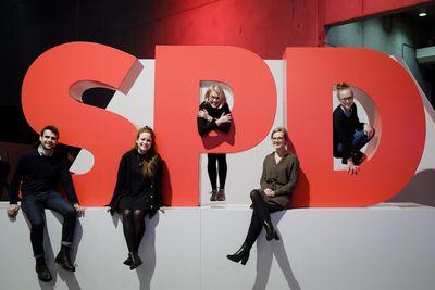 Foto: Junge Menschen sitzen rundum ein großes SPD-Logo