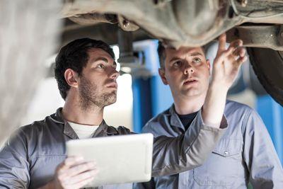 Bild: Männer mit einem Ipad reparieren ein Auto
