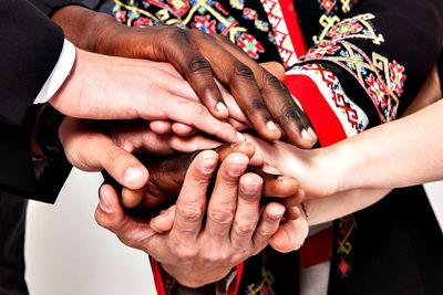 Foto: Menschen verschiedener Nationen schlagen die Hände übereinander
