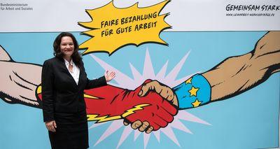 """Foto: Andrea Nahles steht vor einem Plakat mit der Aufschrift """"Faire Bezahlung für gute Arbeit"""""""