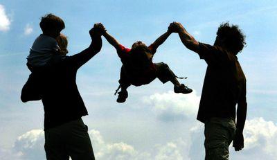 Eltern wirbeln ihr Kind durch die Luft. (Foto: dpa)