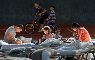 Foto: Auf ihren Feldbetten sitzen Flüchtlinge in der August Schärttner Turnhalle in Hanau (Hessen).