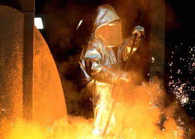 Foto: Ein Stahlarbeiter steht in Duisburg am Hochofen im Thyssenkrupp Werk.