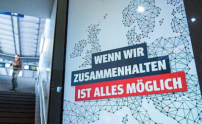 """Foto: """"Wenn wir zusammenhalten ist alles mšglich"""" steht an einem Bahnhof auf einer Werbetafel."""