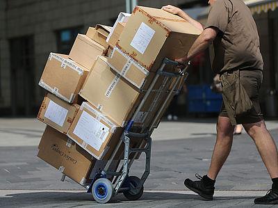 Foto: Ein Paketbote liefert Pakete aus.
