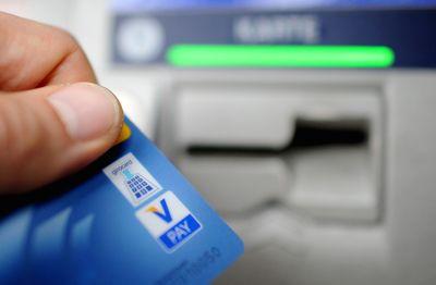 Foto: Bankkunde hebt mit seiner Girokarte Bargeld vom Geldautomaten ab.