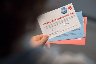 Foto: Ein SPD-Mitglied schaut sich seine Unterlagen für das SPD-Mitgliedervotum zur Bildung einer Großen Koalition mit der Union an.