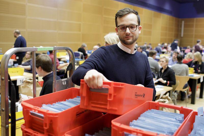 Foto: Ein Freiwilliger nimmt ein Kasten mit Stimmunterlagen zur Auszählung