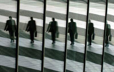 Foto: Ein Mann mit Aktentasche geht in Bonn ins Büro und spiegelt sich dabei in den Glasscheiben der Post-Towers (Archivfoto, Illustration zum Thema Manager)