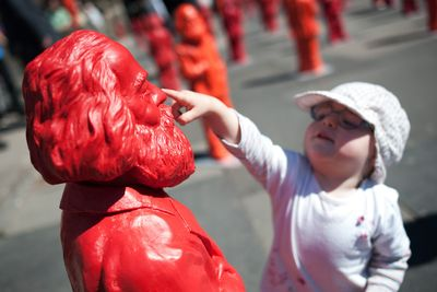 Foto: Ein kleines Mädchen greift einer Karl-Marx-Figur an die Nase.