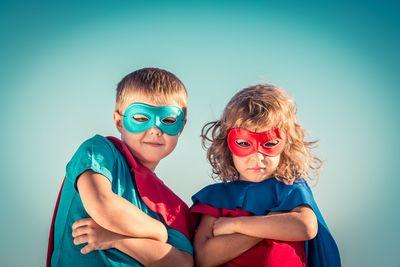 Foto: Ein Junge und ein Mädchen in Superman-Kostümen schauen die Arme verschränkt den Betrachter an.