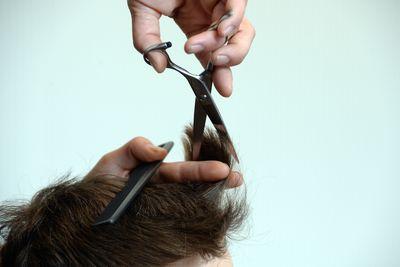 Foto: Ein Friseur schneidet einem Mann die Haare.