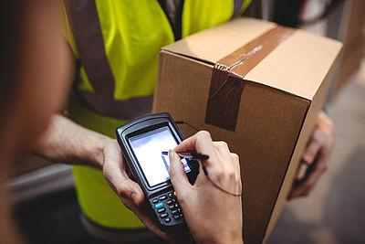 Foto: Paketbotin übergibt ein Paket an Kunden
