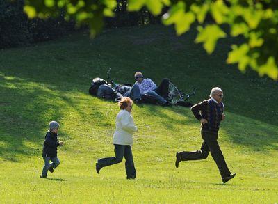 Ein Kind läuft in einem Park hinter seinen Großeltern her.