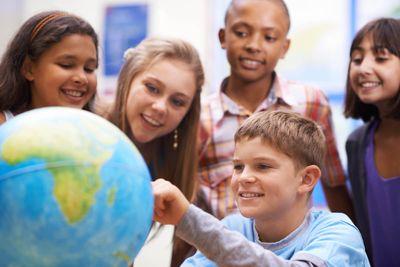 Foto: Schüler stehen an einem Globus und betrachten ihn