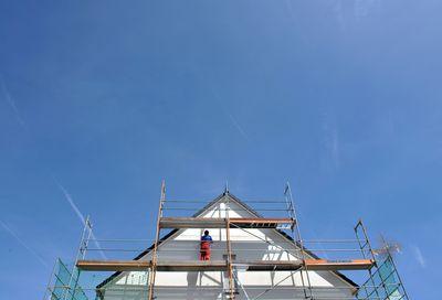 Foto: Ein Arbeiter ist an einer Fassade eines neuen Hauses beschäftigt.