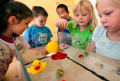 Kinder aus einer Kindertagesstätte in Ilmenau experimentieren mit der Tragfähigkeit von Wasser. (Foto:dpa)