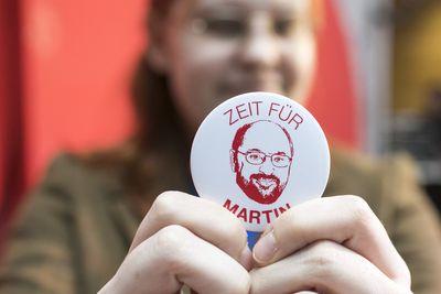 """Foto: Ein martin Schulz-Fan hält stolz einen """"Zeit für Martin""""-Button in den Händen"""