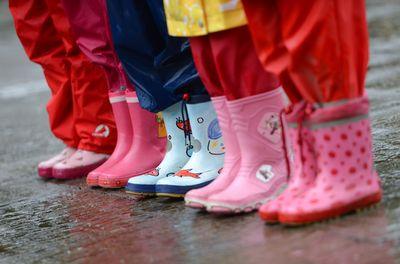 Kinder in Gummistifeln stehen im Regen. (Foto:dpa)