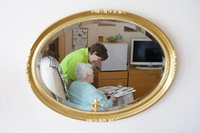 Eine Pflegekraft und eine ältere Dame schauen sich in Weingarten (Kreis Ravensburg) in einem Altenheim gemeinsam ein Fotoalbum an. (Foto: dpa)