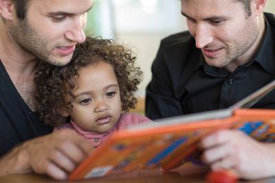 Bild: Zwei Männer lesen ein Buch mit einem Kind
