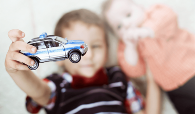 Foto: Kind hält Polizeiwagen neben kleinem Bruder