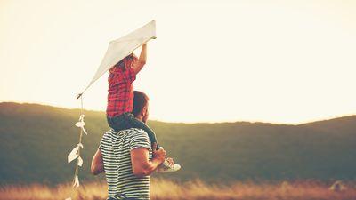 Symbolfoto: Glücklicher Vater und Kind auf der Schulter mit Drachen im Sommer in der Natur
