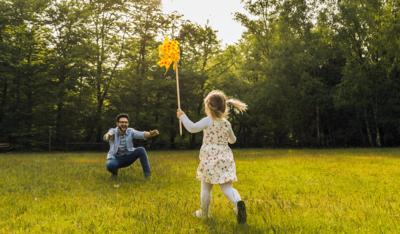 Foto: Vater und Tochter spielen auf einer Wiese