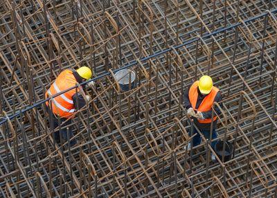 Zwei Arbeiter stehen auf einem Drahgerüst.